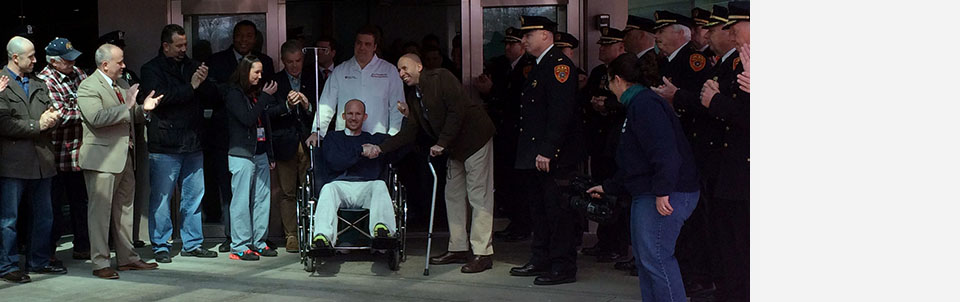 Dr. James Vosswinkel, Chief of Trauma, Emergency Surgery and Surgical Critical Care, escorts Officer Mark Collins out in a wheelchair to over 100 cheering Suffolk County police officers and other supporters